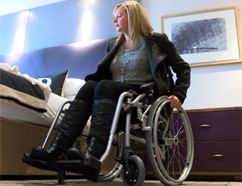 A woman in a wheelchair in a hotel bedroom